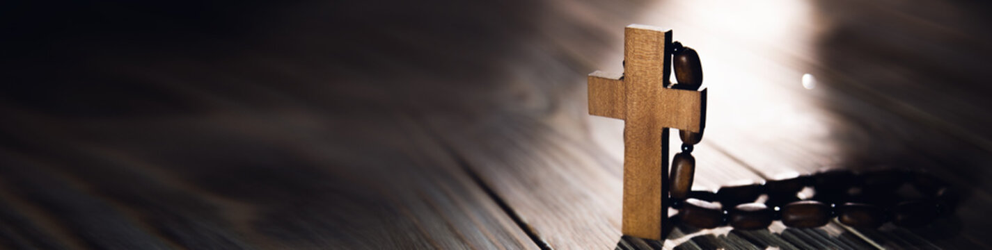 Wooden cross with necklace on table