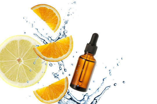 Dark brown glass bottle of face serum with vitamin C or essential oil and orange slices flying in splashing water