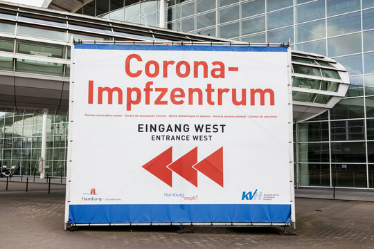 "Sign showing directions for the Corona vaccination center, west entrance (on German: ""Corona Impfzentrum, Eingang West"") center in Hamburg Messehallen, Germany"
