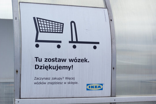 """Katowice, Poland – March 20, 2021: Sing """"Tu zostaw wózek. Dziękujemy! Zaczynasz zakupy? Więcej wózków znajdziesz w sklepie."""" (Eng: Leave your cart here. Thank you! Start shopping? More carts inside)"""