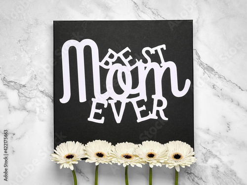 Paper text Best Mom Ever. Greeting card for Mother's day. White gerberas on black square board, natural fresh flowers in a row. Off white marble table. Happy Mothers day