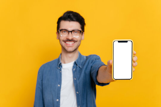 Defocused caucasian unshaven smiling guy with glasses in denim shirt, looks at the camera, holds smartphone with blank white screen in hand, copy space, isolated orange background