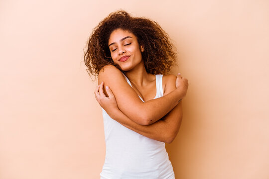 Young african american woman isolated on beige background hugs, smiling carefree and happy.