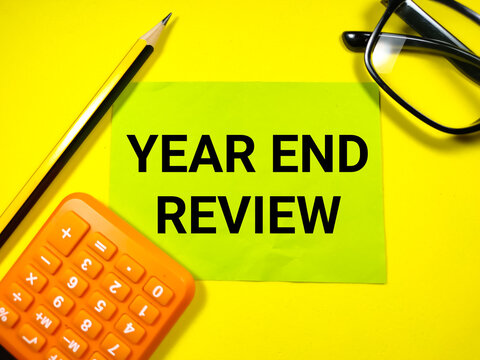 Business concept.Text YEAR END REVIEW on paper note with calculator,glasses and pencil on yellow background.