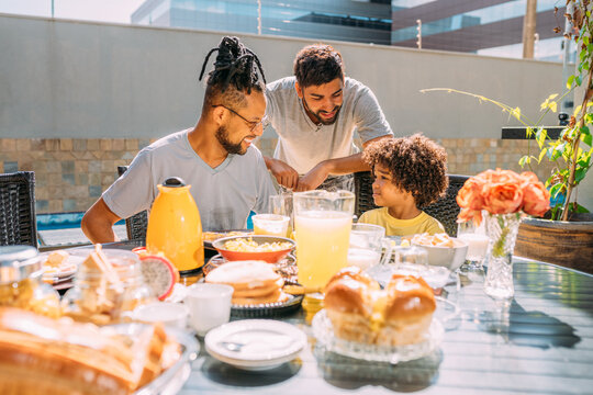Latinx gay couple having breakfast with their curly-haired son