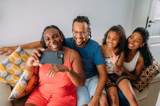 Happy Latinx family making a video call on their cell phone