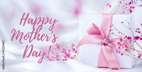Happy mothers day lettering greeting card. Gift box with pink ribbon dry pink flowers. Bright light pastel concept.
