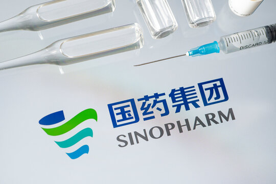 Vials of liquid on a white table and the logo of a large pharmaceutical company.