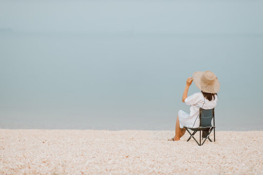Young women sitting relaxing on Chair picnic at the beach looking at the beautiful sea.