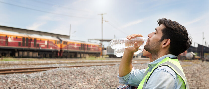 Engineer or male worker is drinking water outdoors.