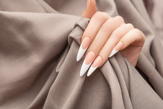 Female hand with long french nail design. Long french nail polish manicure. Woman hand on beige fabric background.