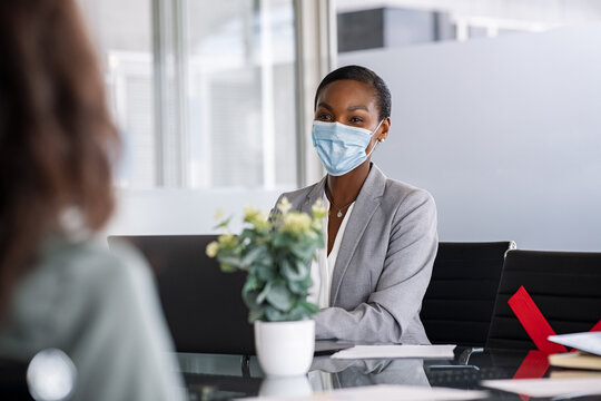 Mature black businesswoman wearing protective face mask in office