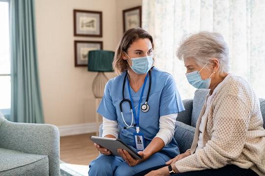 Nurse explaining therapy to senior woman at home visit