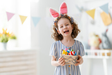 child with Easter painting eggs