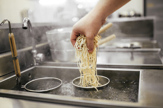 Cooking egg noodles in the boiling baskets on the kitchen