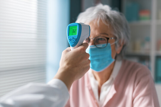 Doctor checking a senior patient's body temperature