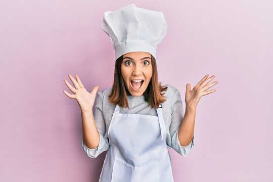 Young beautiful woman wearing professional cook uniform and hat celebrating crazy and amazed for success with arms raised and open eyes screaming excited. winner concept
