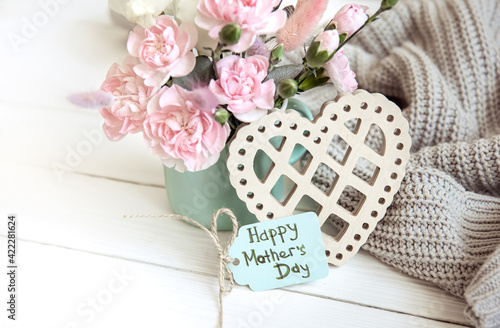 Cozy spring still life with fresh flowers and a decorative heart for Mother's Day.