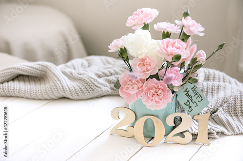 Cozy spring still life with fresh flowers and decorative number 2021 for mother's day.