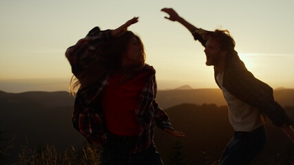 Joyful guy and girl jumping in air outdoor. Man and woman dancing in mountains