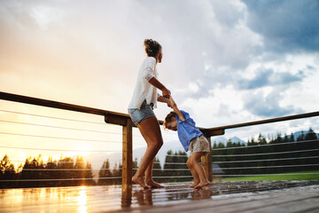 Obraz Mother with small daughter playing in rain on patio of wooden cabin, holiday in nature concept. - fototapety do salonu