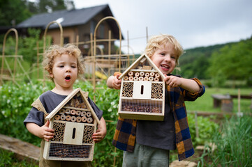 Small boy and girl holding bug and insect hotel in garden, sustainable lifestyle.