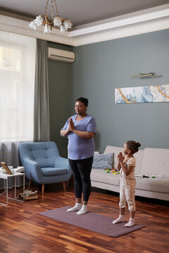 Vertical full length portrait of African-American woman doing yoga at home with cute little girl, copy space