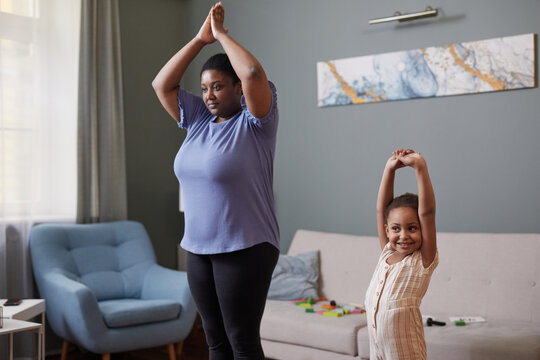 Candid waist up portrait of African-American mother and daughter doing yoga together at home, copy space