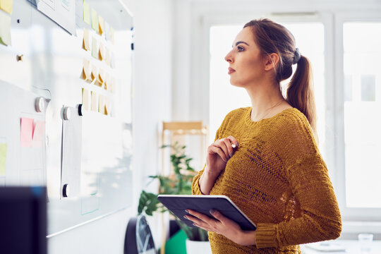 Businesswoman looking at whiteboard in office