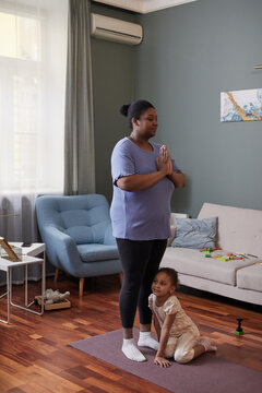 Vertical full length portrait of African-American woman doing yoga at home with little girl