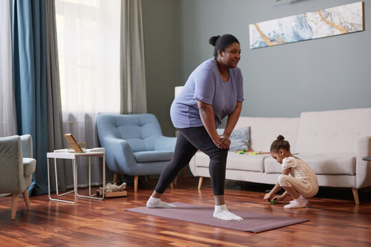 Full length portrait of African-American woman working out at home with little girl in background, copy space