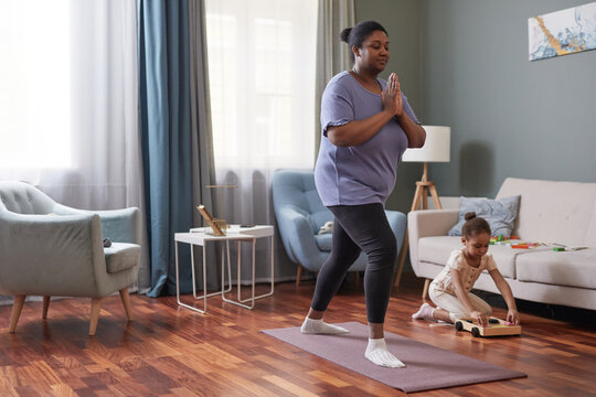 Full length portrait of African-American woman doing yoga at home with little girl in background, copy space