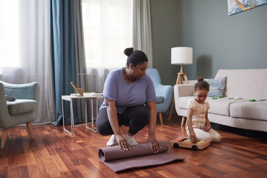 Full length portrait of African-American woman unrolling yoga mat for home workout with little girl, copy space