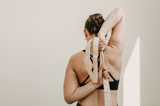 Partial upper body portrait of woman doing gomukasana arms yoga pose using a cotton strap for active stretching and muscle activation on a white background. Self care practices at home