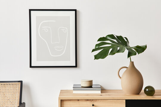 Stylish interior of living room with mock up poster frame, wooden commode, book, tropical leaf in ceramic vase and elegant personal accessories. Minimalist concept of home decor. Template.