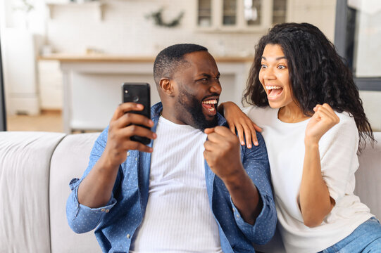 Excited and overjoyed African-American young couple sits on the couch at home and holds smartphone, a man and woman show victory gesture, celebrating good news or win, received money on account