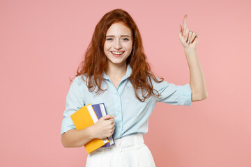 Young insighted proactive redhead student woman in blue shirt hold book index finger up great new idea isolated on pastel pink background studio portrait Education school university college concept.