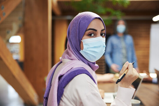 Muslim businesswoman wearing a face mask in a meeting