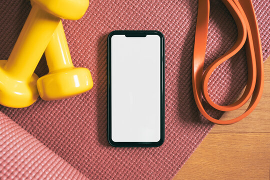 Mobile phone with white screen next to fitness accessories. Training, being fit at home in lockdown: fitness phone app, yoga mat, fitness gum and barbells