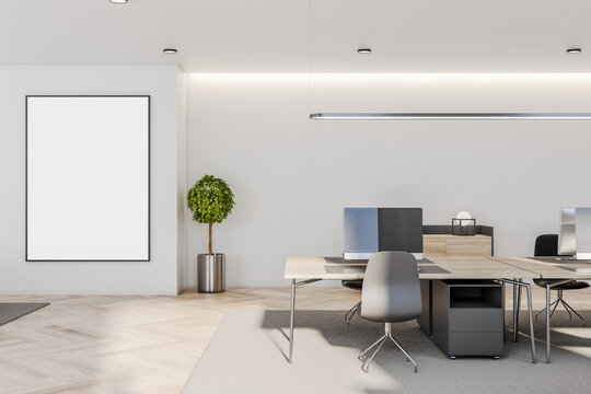 Blank white poster in black picture frame on light wall in sunny spacious office with wooden furniture and floor and tree in metallic flowerpot. Mock up