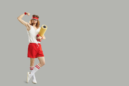 Full body funny goofy silly stupid skinny nerd in gym sweatband standing holding sports mat and dumbbells and showing weak bicep. Fitness workout advertising copyspace background, empty space for text