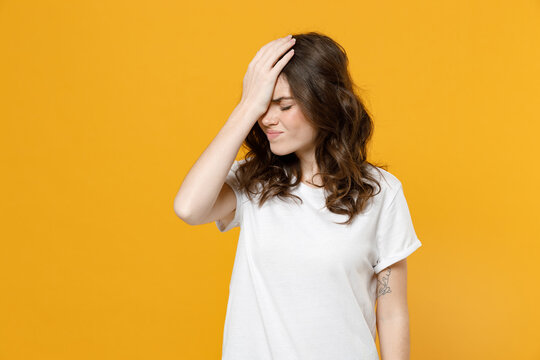 Young mistaken tired disappointed caucasian student woman 20s wearing white basic casual t-shirt put hand on face facepalm epic fail gesture isolated on yellow orange color background studio portrait.
