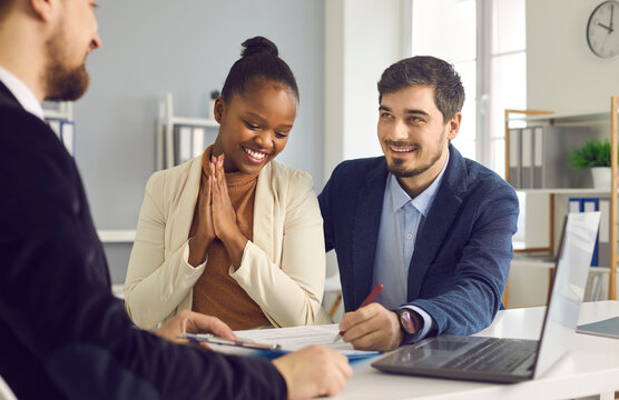 Interracial couple buys real estate. Happy caucasian husband and his dark-skinned wife sign a document while sitting in a bank office. Concept of buying a home or getting mortgage approval.