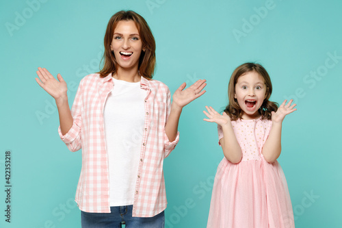 Happy woman in pink clothes have fun with cute child baby girl 5-6 years old Mommy little kid daughter spreading hands isolated on pastel blue azure background studio Mother's Day love family concept