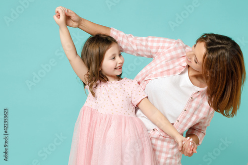 Happy woman in pink clothes have fun with cute child baby girl 5-6 years old. Mommy little kid daughter dancing celebrate isolated on pastel blue background studio. Mother's Day love family concept.