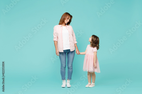 Full length happy woman in pink clothes have fun with cute child baby girl 5-6 years old. Mommy little kid daughter isolated on pastel blue azure background studio. Mother's Day love family concept.