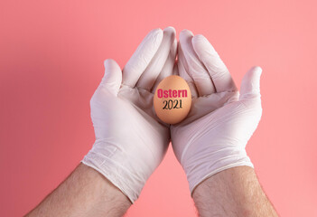 Hand in protective gloves holding egg with Ostern 2021 text