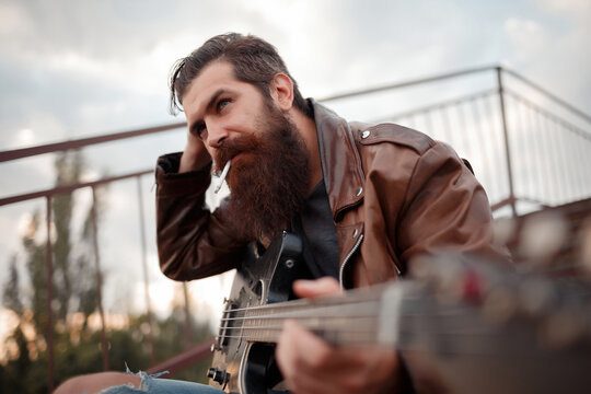 a man with a long red beard and gray hair in a brown leather jacket holds an electric guitar in his hand and smokes a cigarette close-up