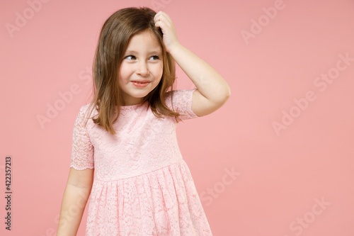 Little thoughtful cute kid girl 5-6 years old wears rosy dress have fun put hand on head isolated on pastel pink background child studio portrait. Mother's Day love family childhood lifestyle concept.