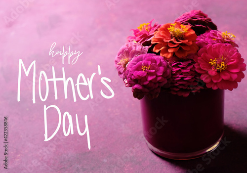 Bouquet of zinnia flowers with Mother's Day greeting on purple background.